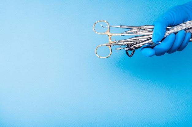 Main dans un gant bleu tenant des outils dentaires de chirurgie sur fond bleu clair