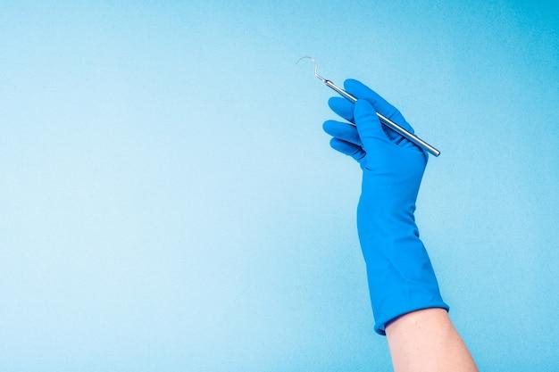 Main dans un gant bleu tenant une pince dentaire sur fond bleu clair