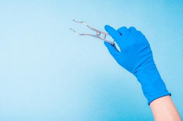 Main dans un gant bleu tenant des pinces dentaires en métal sur fond bleu clair