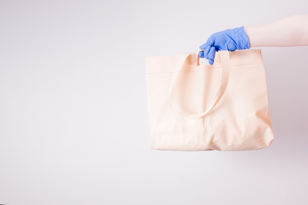 Une main dans un gant en caoutchouc bleu tient un sac à provisions, fond clair, espace copie, concept de livraison sans contact