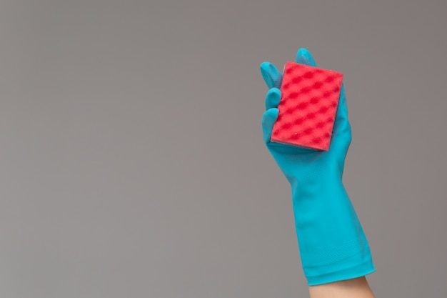 Main dans un gant en caoutchouc contient une éponge de lavage de couleur sur fond neutre