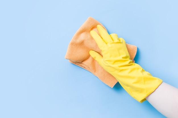 La main dans un gant en caoutchouc jaune lave le mur avec un chiffon doux orange, nettoie et lave les murs