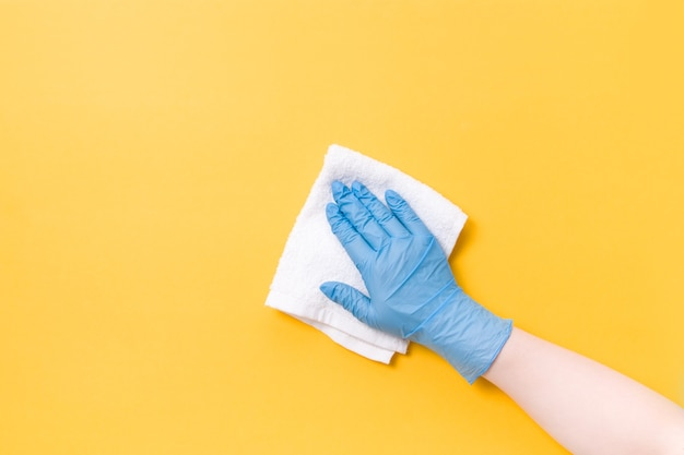 La main dans le gant en caoutchouc jetable bleu lave la surface
