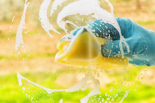 Main dans un gant en caoutchouc lave une fenêtre