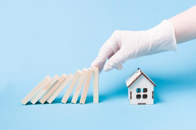 La main dans un gant en caoutchouc médical blanc empêche un domino de tomber devant un modèle de maison en bois