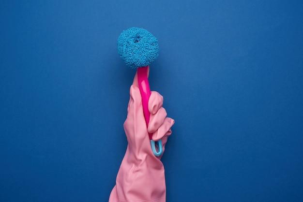 La main dans un gant en caoutchouc rose pour nettoyer une maison tient une brosse en plastique