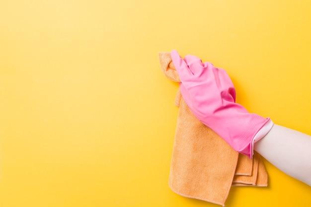 La main dans un gant en caoutchouc rose tient un chiffon orange pour le lavage et le nettoyage