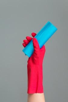 Main dans un gant en caoutchouc tient le sac à ordures coloré sur gris