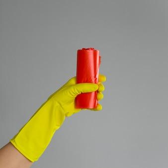 Main dans un gant en caoutchouc tient le sac à ordures coloré