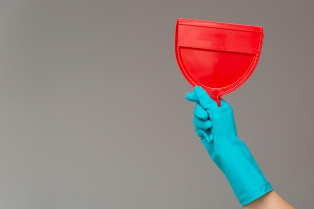Une main dans un gant de caoutchouc tient un scoop