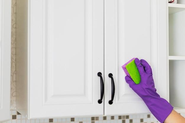 Main dans un gant en caoutchouc violet nettoyant les armoires de cuisine blanches
