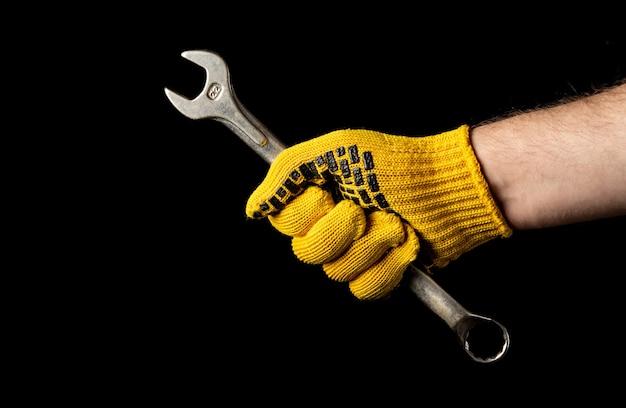 Main dans un gant de construction tenant une clé isolée
