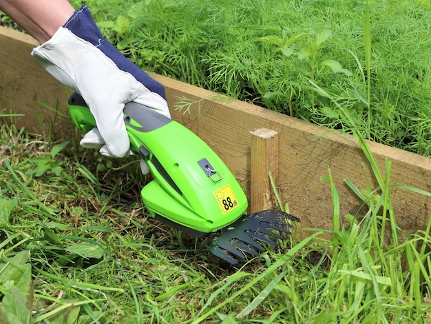 La main dans le gant de jardinage en cuir tient le coupe-herbe à main électrique