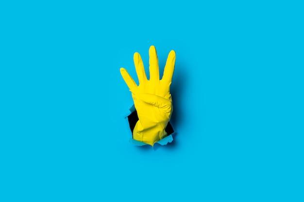 La main dans un gant jaune montre quatre doigts sur un bleu vif