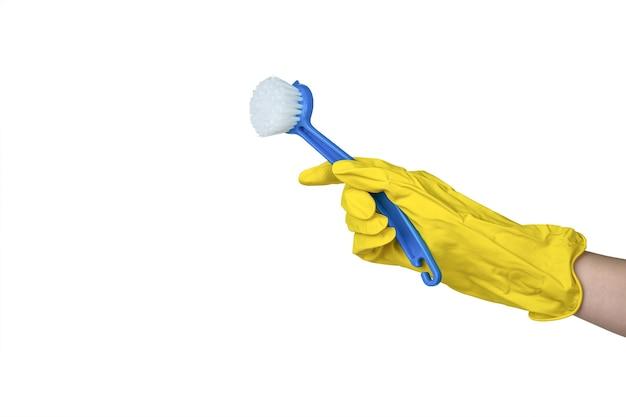 Une main dans un gant jaune avec un pinceau bleu isolé sur un blanc. un article pour nettoyer la maison.
