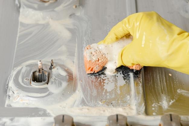 Main dans un gant jaune serrant une éponge orange.