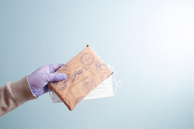 Une main dans un gant jetable en caoutchouc bleu tient un masque protecteur et un cadeau emballé dans du papier kraft