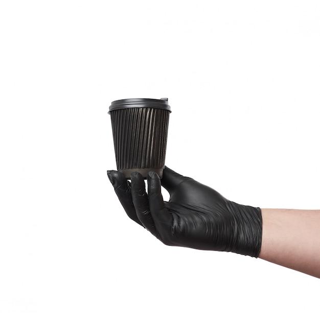 La main dans un gant en latex noir tient une tasse en carton jetable et