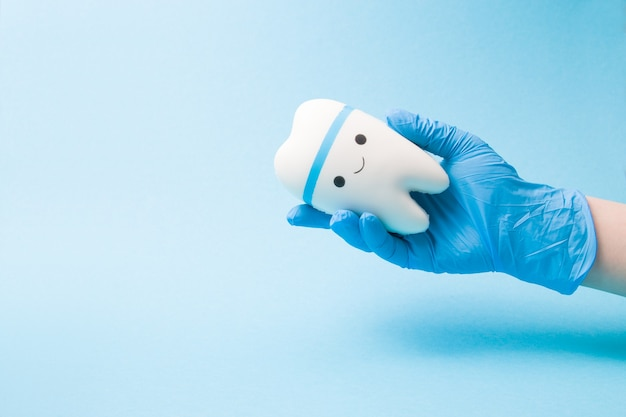 La main dans un gant médical en caoutchouc jetable bleu tient un jouet dent souriante sur une surface bleue