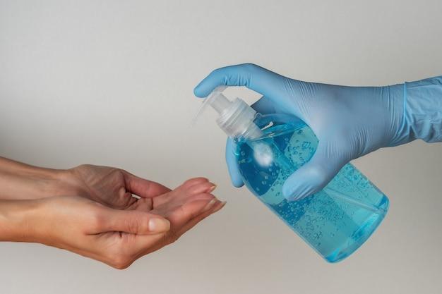 La main dans un gant médical avec un désinfectant pour les mains dans une bouteille sur blanc.
