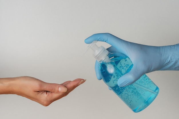 Main dans un gant médical avec un désinfectant pour les mains dans une bouteille sur fond blanc.