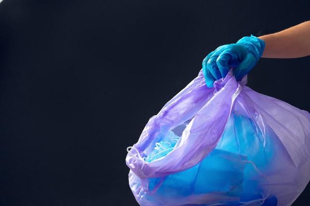 Main dans un gant médical jetant un sac poubelle