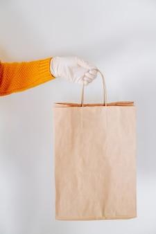 La main dans un gant médical avec un sac de livraison en papier