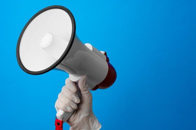 Main dans un gant médical tenant haut-parleur contre bleu