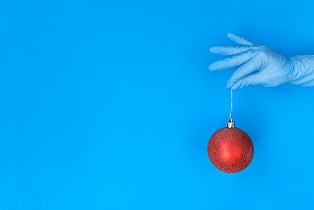 La main dans le gant médical tient la boule de noël rouge sur fond bleu avec espace de copie.