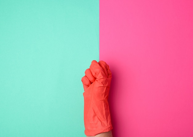 La main dans un gant orange en caoutchouc pour nettoyer une maison serrée dans un poing