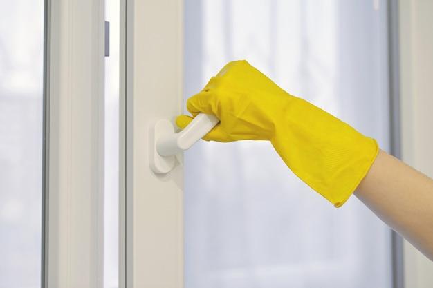 La main dans le gant de protection en caoutchouc jaune ouvre et ferme la fenêtre en plastique pvc. nettoyage, entretien et réparation.