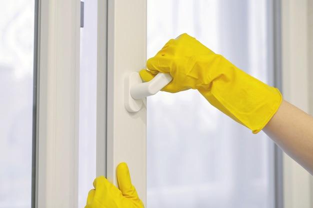 Main dans un gant de protection en caoutchouc jaune ouvre et ferme la fenêtre en plastique, pvc