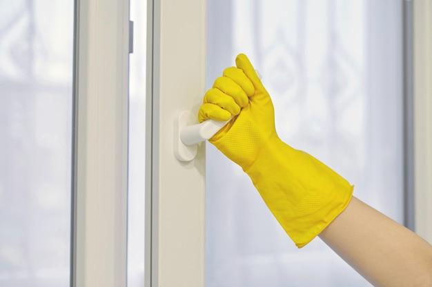 La main dans un gant de protection en caoutchouc jaune ouvre et ferme la fenêtre en plastique pvc