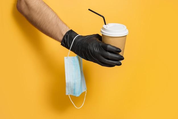 Une main dans un gant de protection avec un masque médical au poignet tient une tasse en papier sur fond jaune.