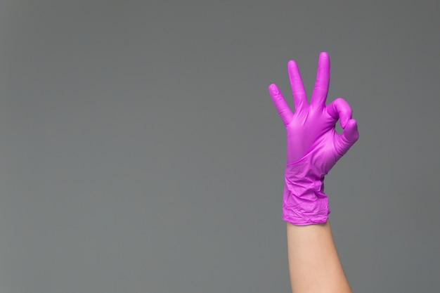 La main dans le gant en silicone rose montre le signe ok.
