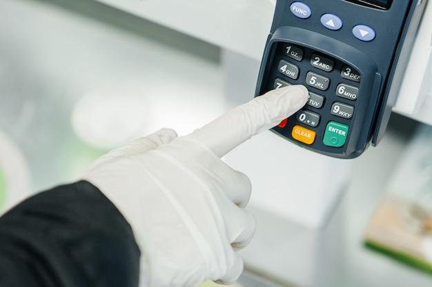 Main dans le gant avec terminal de paiement, respect des règles de sécurité en cas d'épidémie