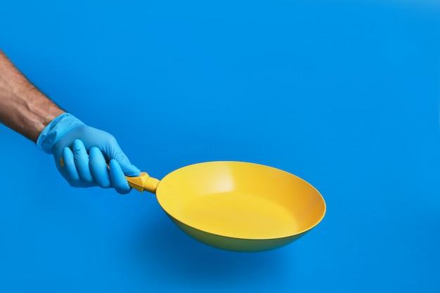 La main dans le gant tient une poêle jaune sur un fond coloré.