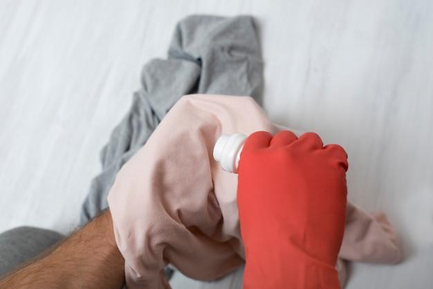 La main dans le gant verse un liquide pour le lavage des vêtements. fermer