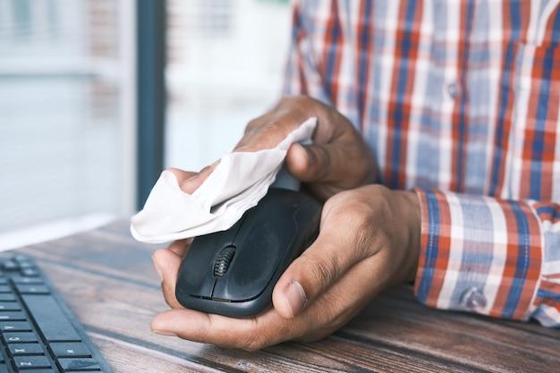 Main dans des gants en caoutchouc bleu et souris d'ordinateur désinfectant les tissus blancs