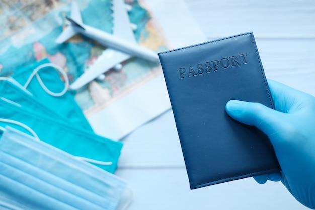 Main dans des gants chirurgicaux bleus tenant le passeport en main.