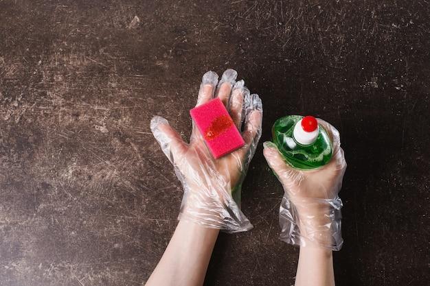 La main dans des gants hygiéniques en plastique avec une éponge sur un fond de marbre foncé. ranger la maison. laver la vaisselle avec du détergent