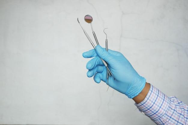 Main dans des gants en latex tenant du matériel dentaire