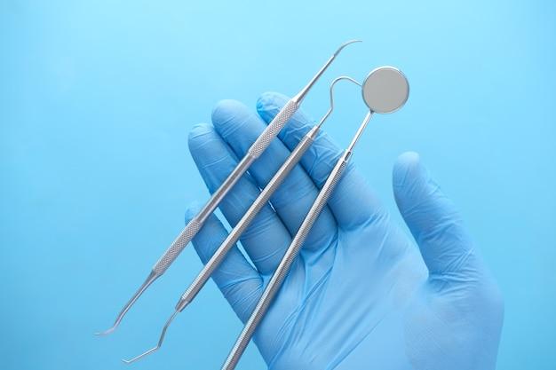 Main dans des gants en latex tenant un équipement dentaire