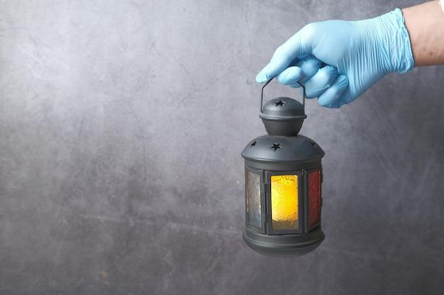 Main dans les gants tenant la lumière de la lanterne contre le mur noir