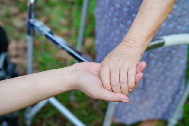 Main dans la main asiatique vieille ou âgée vieille dame patiente avec amour