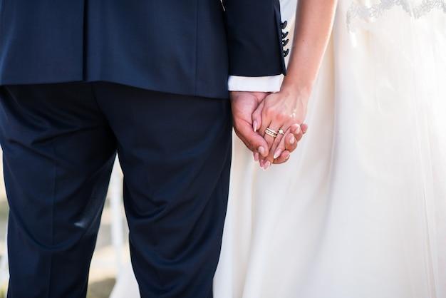 Main dans la main du couple de mariage