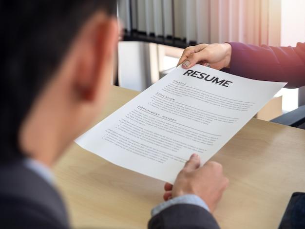 Main dans la main du demandeur donnant cv à l'employeur pour examiner le profil