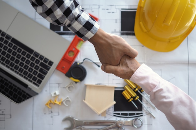 Main dans la main entre les entrepreneurs du projet et les clients en raison de la négociation des dépenses et des investissements