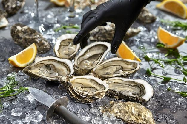 La main dans la main pour chercher des huîtres servies dans des coquilles ouvertes