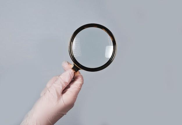 Main dans la main tenir une loupe pour trouver et examiner les maladies avec du verre optique